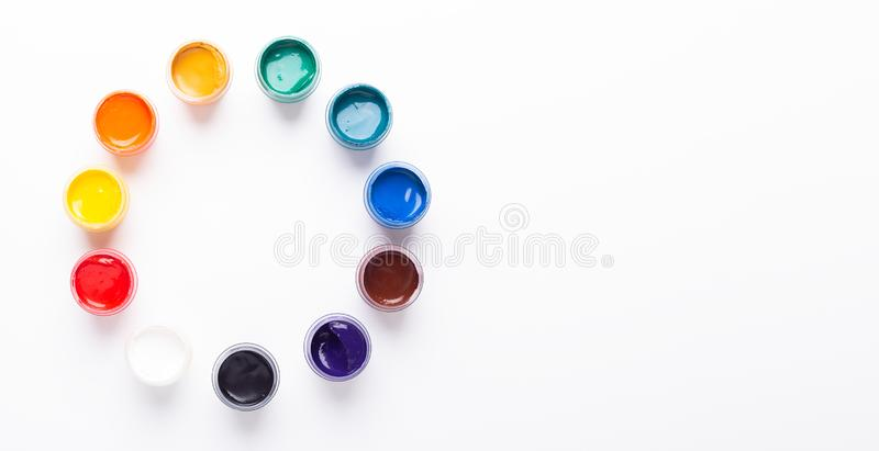 Multicolored gouache on a white background Circle shape Isolated Paints in containers Top view Banner Horizontal. Multicolored gouache on a white background stock photo