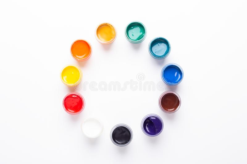 Multicolored gouache on a white background Circle shape Isolated Paints in containers Top view. Copy space stock image