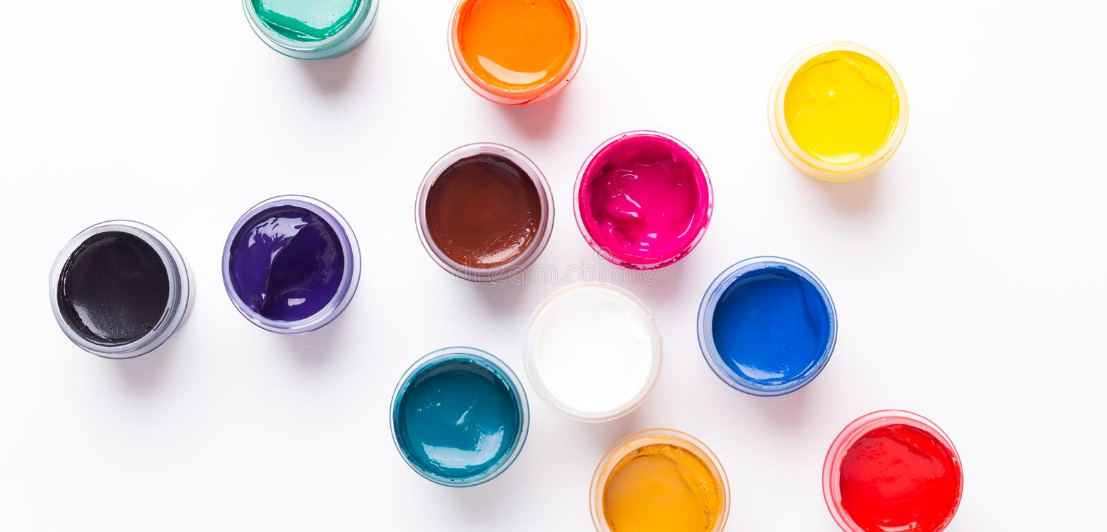 Multicolored gouache on a white background Isolated Paints in containers Top view Banner Horizontal. Multicolored gouache on a white background Isolated Paints royalty free stock photos