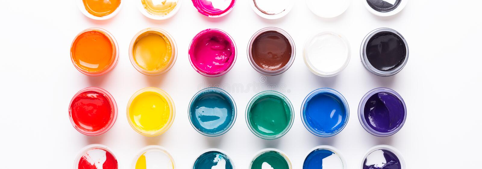 Multicolored gouache on a white background Isolated Paints in containers Top view Banner Horizontal. Multicolored gouache on a white background Isolated Paints royalty free stock photo