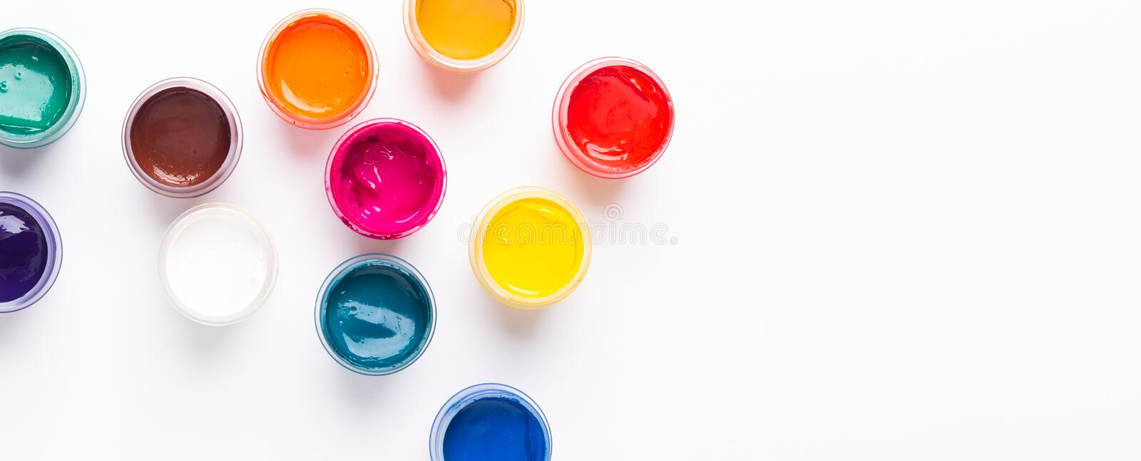 Multicolored gouache on a white background Isolated Paints in containers Top view Banner Horizontal. Multicolored gouache on a white background Isolated Paints royalty free stock images