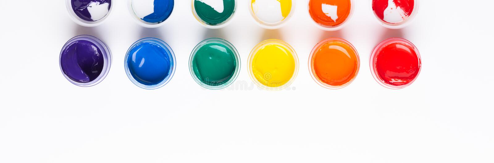 Multicolored gouache on a white background Isolated Paints in containers Top view Banner Horizontal. Multicolored gouache on a white background Isolated Paints royalty free stock image