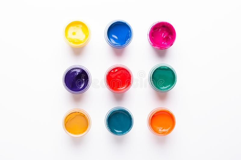 Multicolored gouache on a white background Paints in containers Top view. Copy space stock images