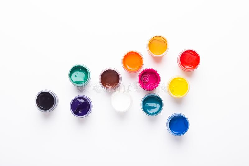 Multicolored gouache on a white background Isolated Paints in containers Top view. Copy space royalty free stock photo