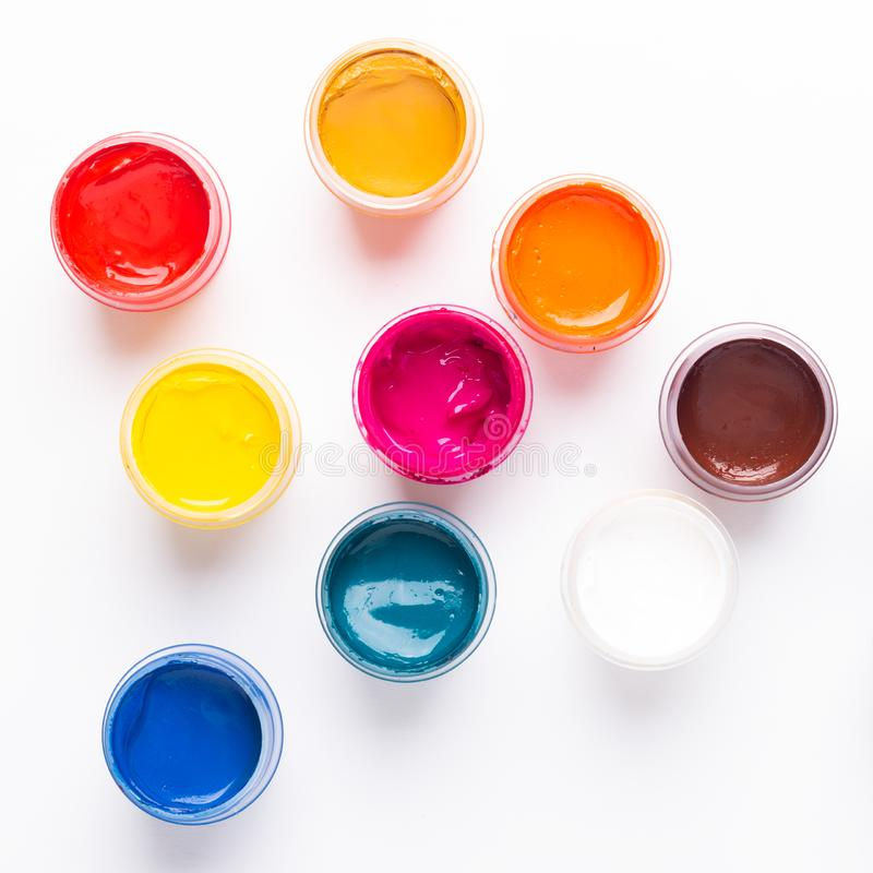 Multicolored gouache on a white background Isolated Paints in containers Top view. Copy space stock photos