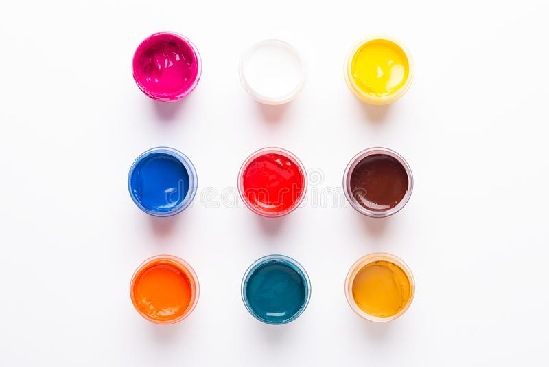 Multicolored gouache on a white background Isolated Paints in containers Top view. Copy space royalty free stock images