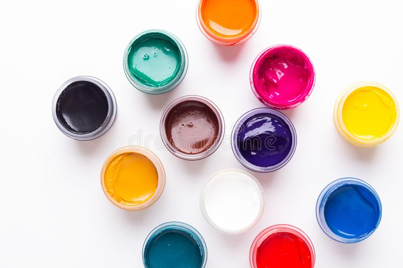 Multicolored gouache on a white background Isolated Paints in containers Top view. Copy space stock image