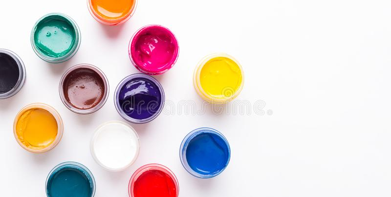 Multicolored gouache on a white background Isolated Paints in containers Top view. Copy space royalty free stock photography