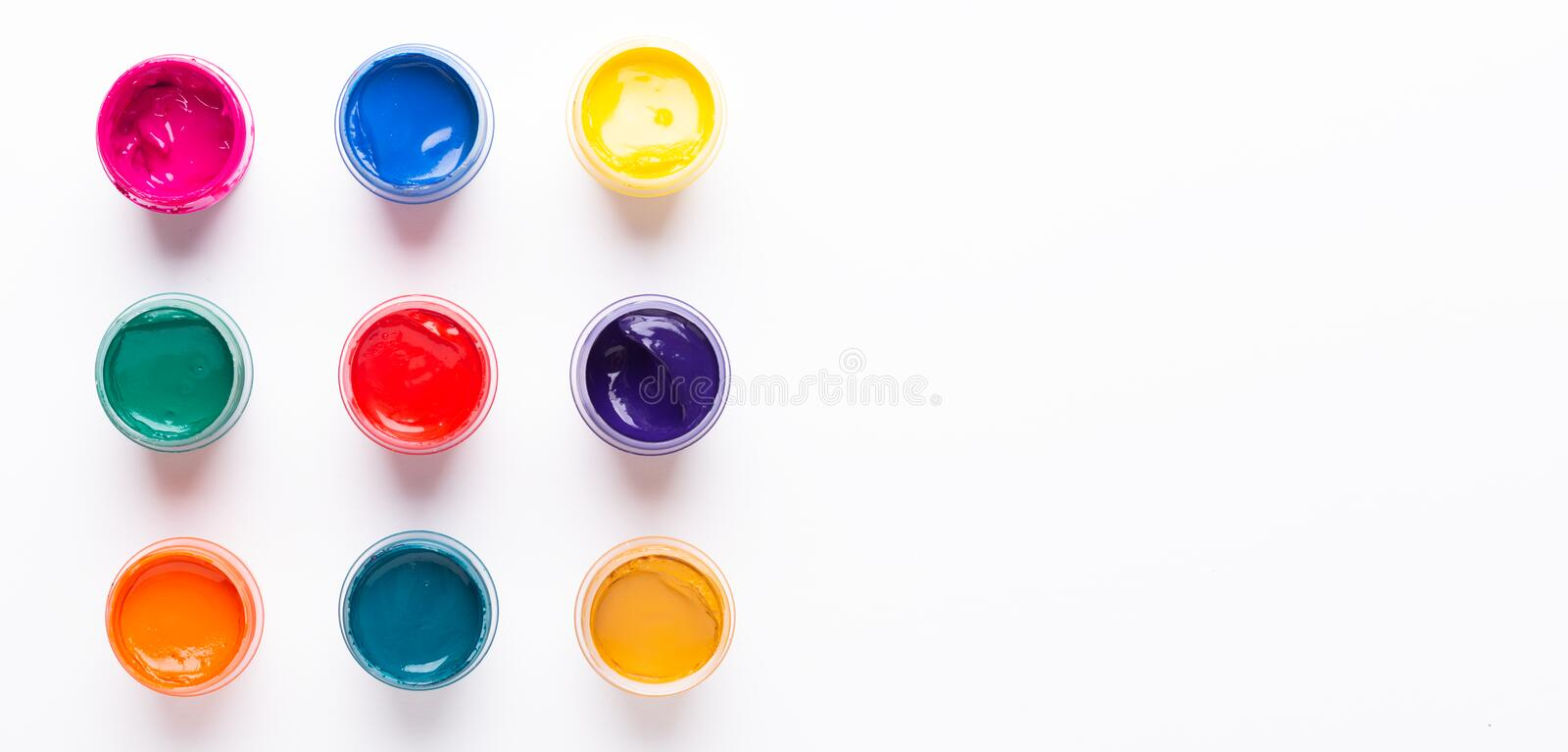 Multicolored gouache on a white background Paints in containers Top view. Copy space Banner Horizontal stock photo