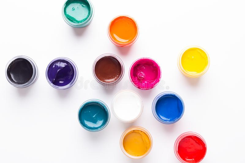 Multicolored gouache on a white background Isolated Paints in containers Top view. Copy space royalty free stock photos