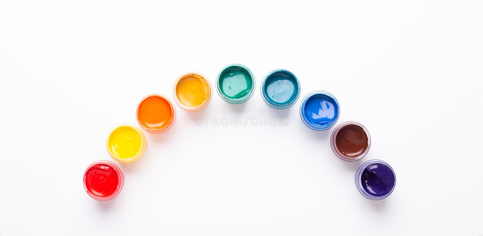 Multicolored gouache on a white background Rainbow shape Isolated Paints in containers Top view Banner Horizontal. Multicolored gouache on a white background royalty free stock images