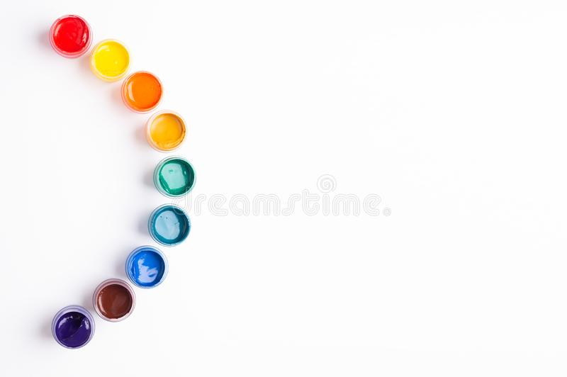 Multicolored gouache on a white background Rainbow shape Isolated Paints in containers Top view Banner Horizontal. Multicolored gouache on a white background stock photography