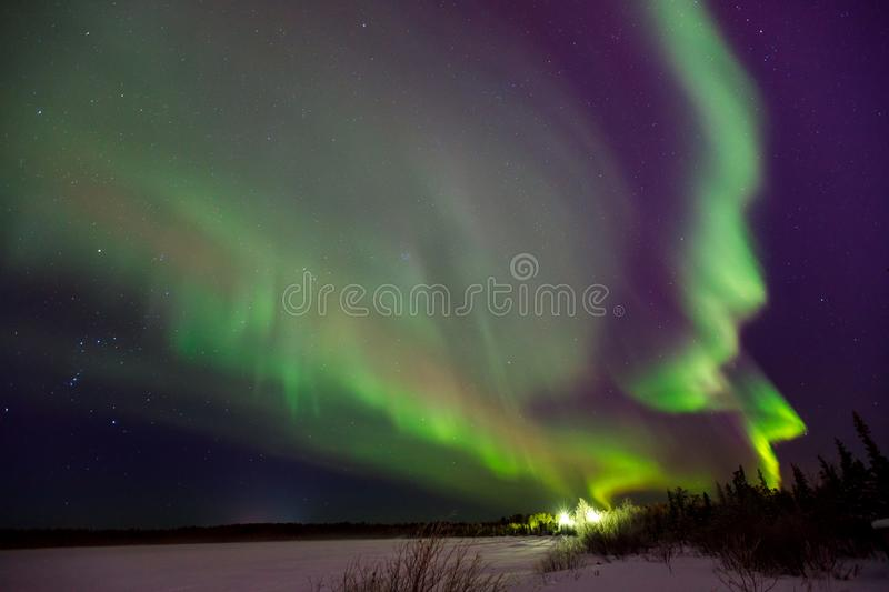 Multicolored green Violet vibrant Aurora Borealis Polaris, Northern Lights in night sky. stock images