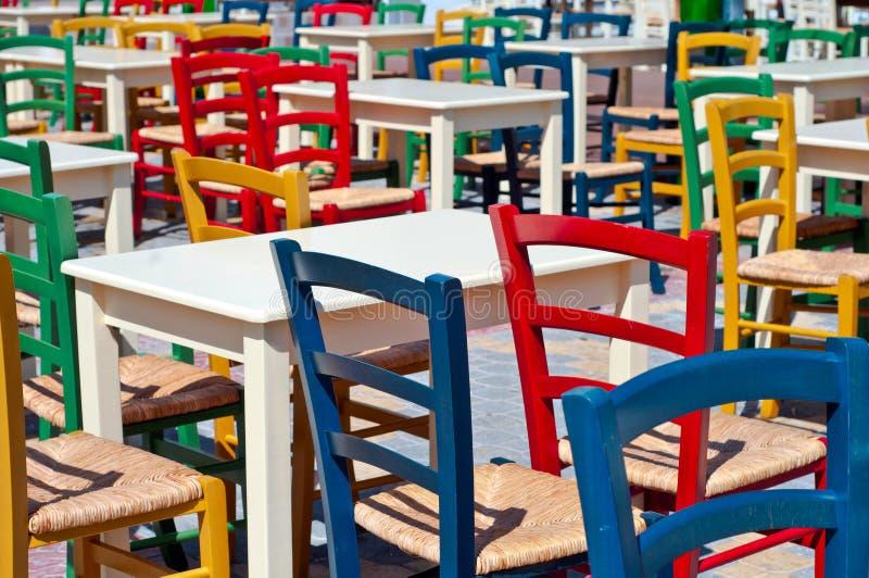 Multicolored Griekse stoelen in de openluchtkoffie stock fotografie