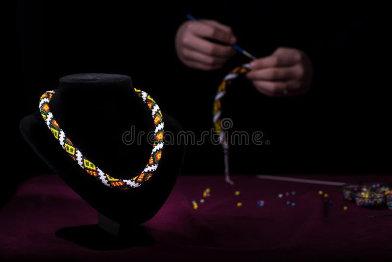 Multicolored halsband van parels op een ledenpop Op het achter zwarte vliegtuig breit het meisje de parels stock fotografie