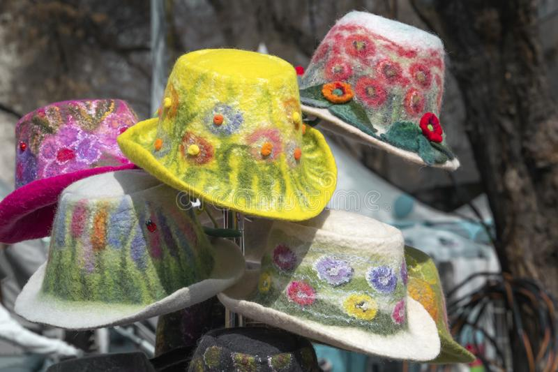 Multicolored handmade women`s hats made of felt with decorations and embroidery are sold in the shop royalty free stock photo