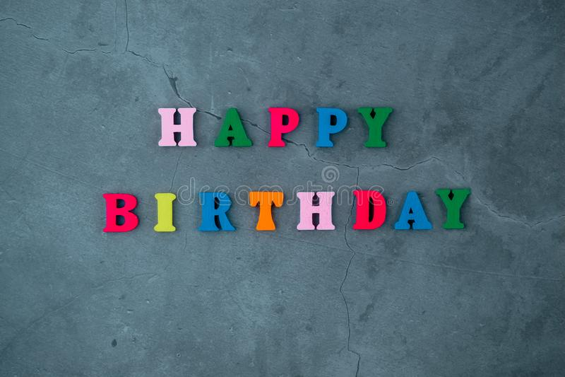 The multicolored happy birthday word is made of wooden letters on a grey plastered wall background royalty free stock photo