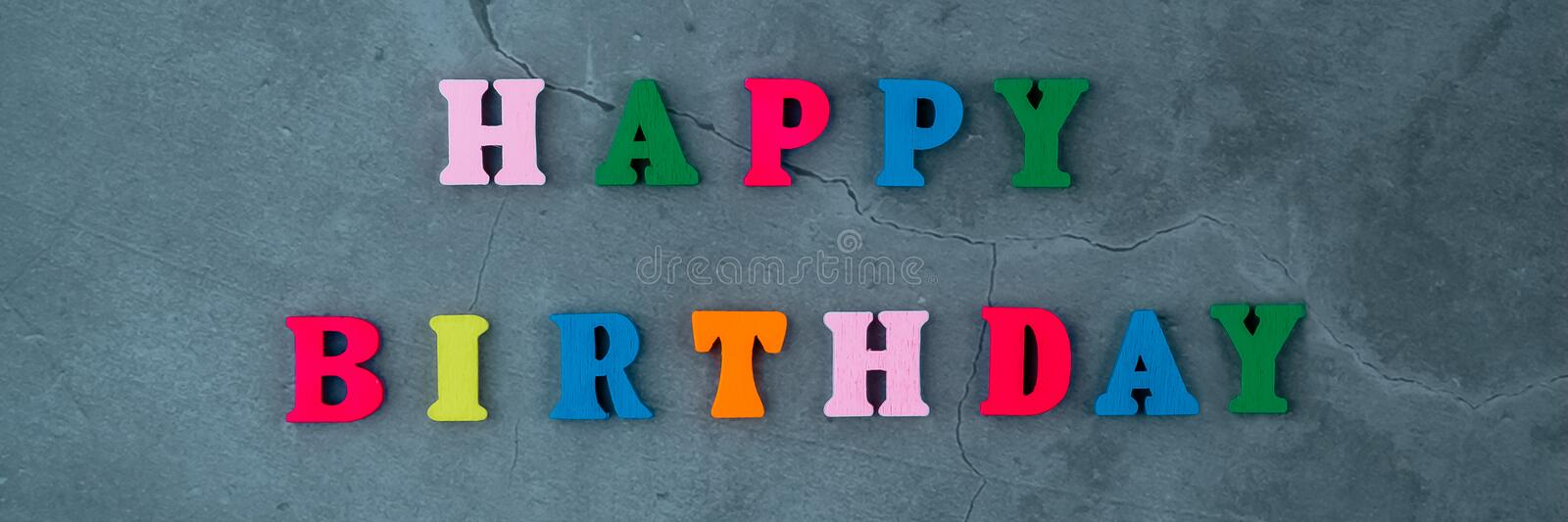 The multicolored happy birthday word is made of wooden letters on a grey plastered wall background. The multicolored happy birthday word is made of wooden royalty free stock photos