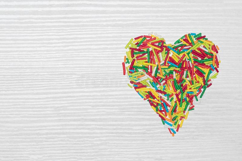 Multicolored heart isolated on white wooden background. Multicolored heart shaped sticks isolated on white wooden background with copy space stock photos