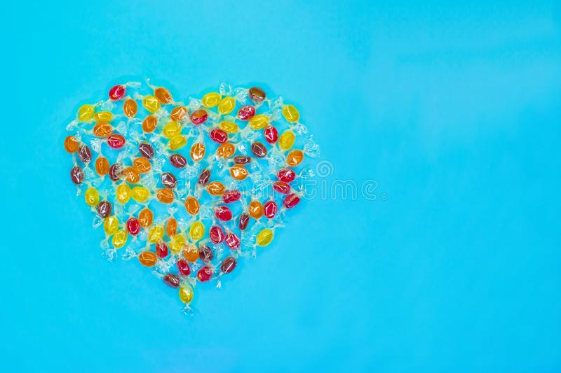 Multicolored heart shaped candies with electric blue background stock photography