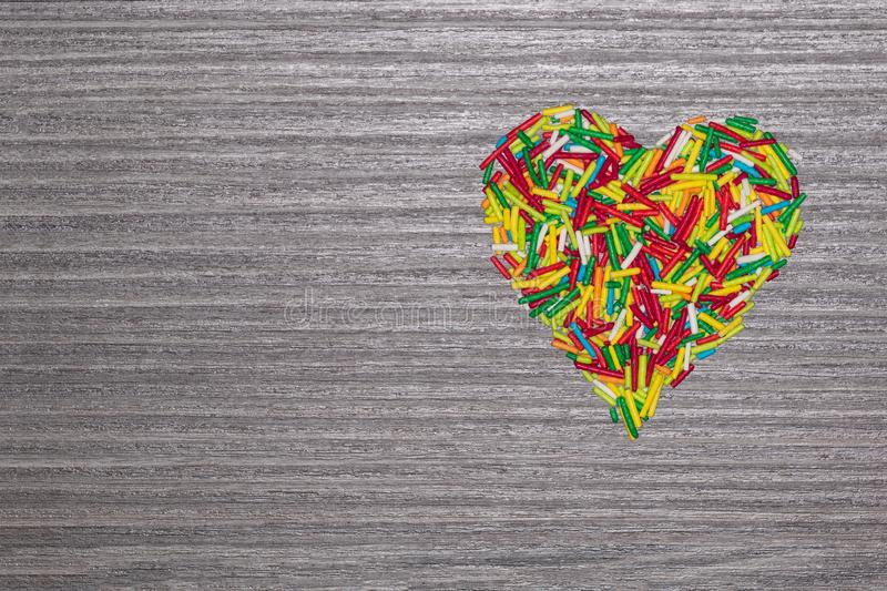 Multicolored heart isolated on grey wooden background. Multicolored heart shaped sticks isolated on grey wooden background with copy space stock image