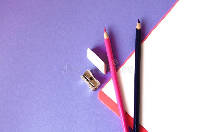 Multicolored, heldere, kleurrijke potloden worden gevestigd bij de bodem schuin en een notitieboekje voor uw tekst op een violett stock fotografie