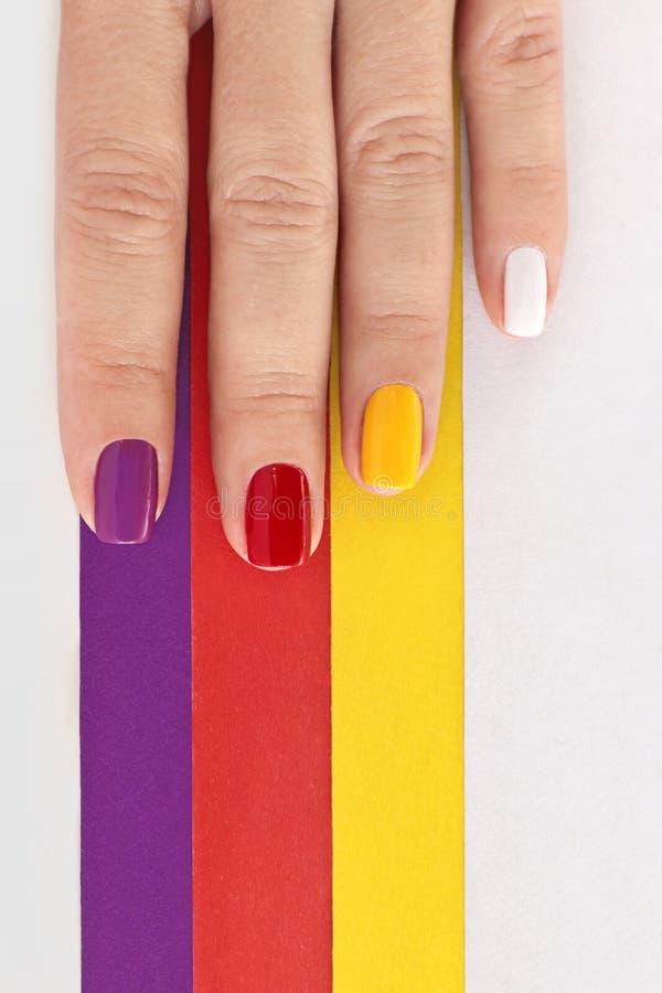 Multicolored heldere verzadigde manicure op kort spijkersclose-up royalty-vrije stock foto