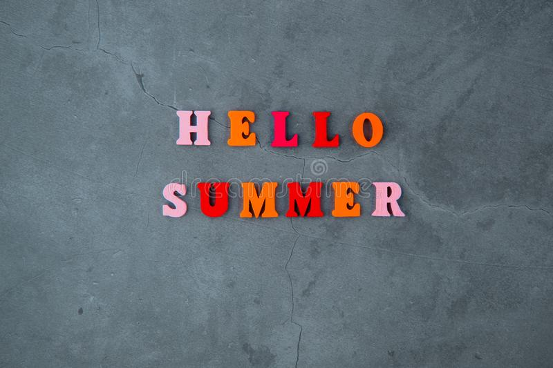 The multicolored hello summer word is made of wooden letters on a grey plastered wall background.  stock photography