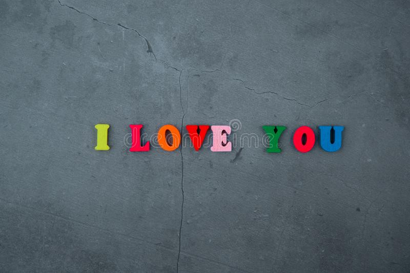 The multicolored I love you word is made of wooden letters on a grey plastered wall background.  stock image