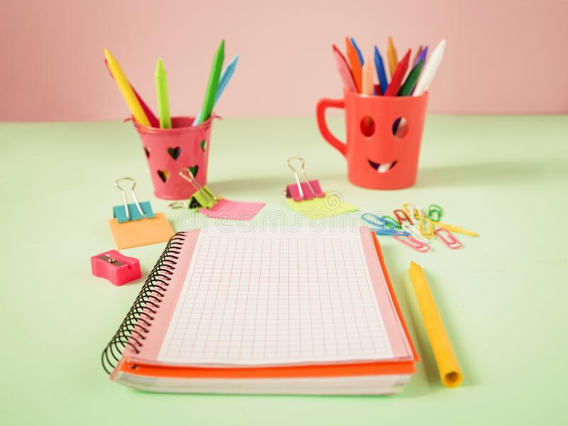 Multicolored image with a white notebook and school material in pastel colors. Multicolored image with a white notebook and drawing material stock images