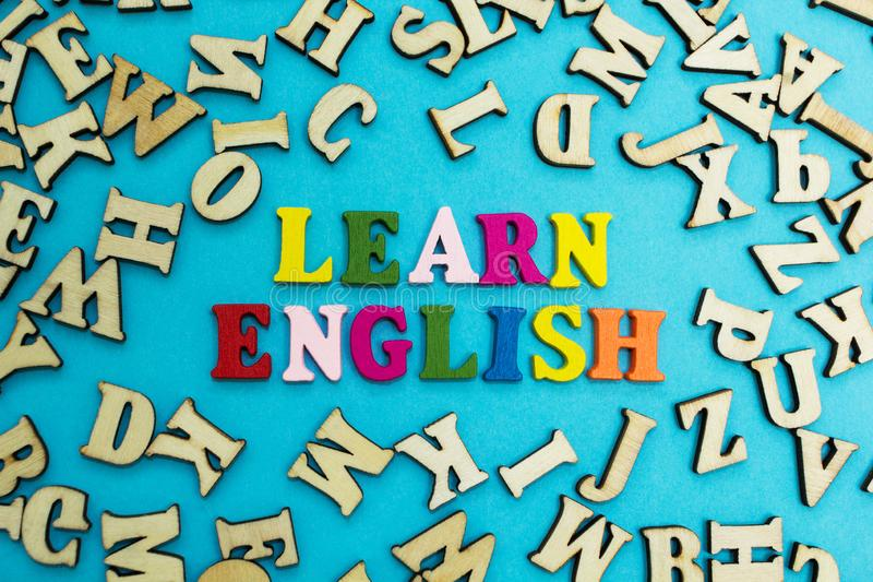 Multicolored inscription `learn English` on a blue background, scattered letters.  royalty free stock images