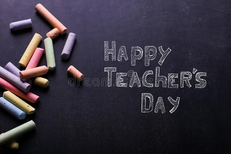 Multicolored kleurpotloden liggen op een zwart bord, exemplaarruimte Het concept school, onderwijs en kinderjaren stock afbeeldingen