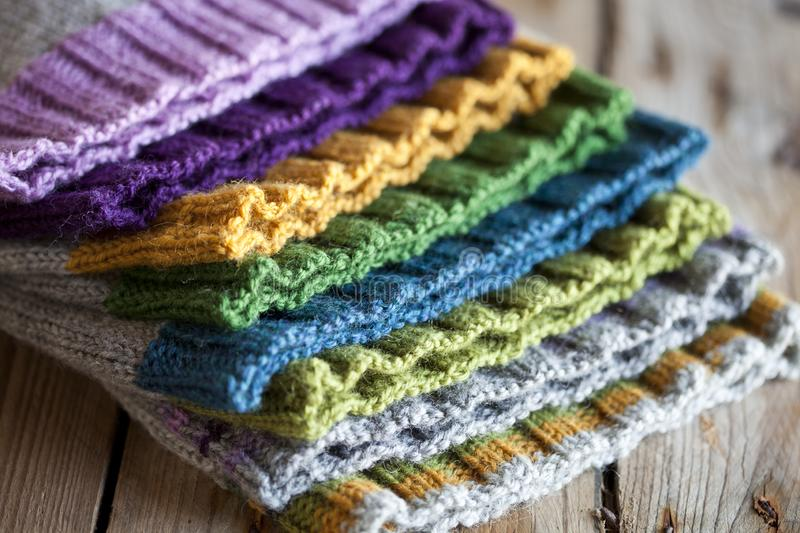 Multicolored knitted hats. Closeup on wooden background royalty free stock images