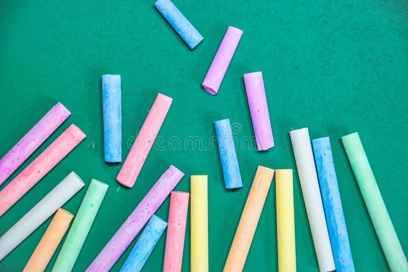 Multicolored krijt op een groen bord stock afbeelding