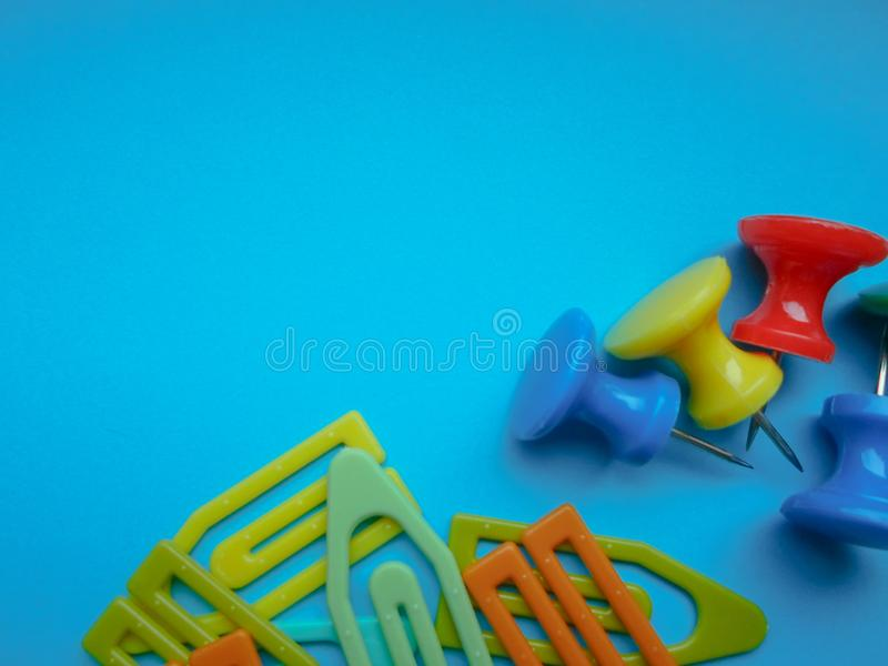 Multicolored latch clips scattered across a turquoise background. View from above. The concept is time to school. Multicolored latch clips scattered across a royalty free stock photos