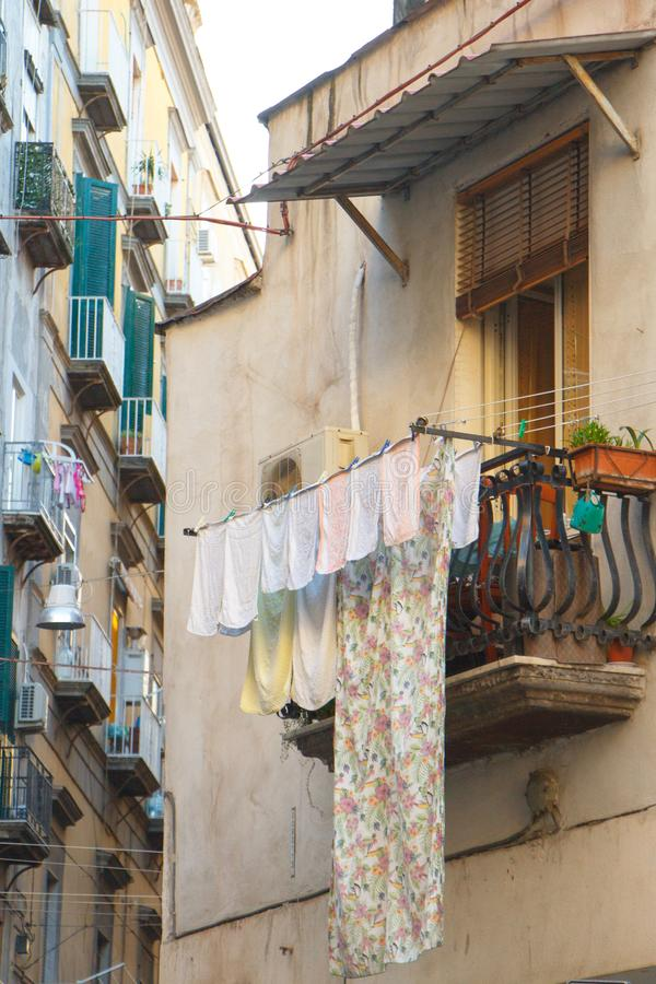 Multicolored laundered clothes are dried on the balcony in the alley of Naples, self-catering and environmental friendliness. Copyspace royalty free stock image