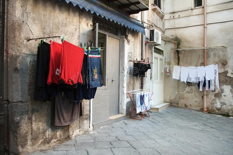 Multicolored laundered clothes are dried on the balcony in the alley of Naples, self-catering and environmental friendliness. Copyspace royalty free stock photo
