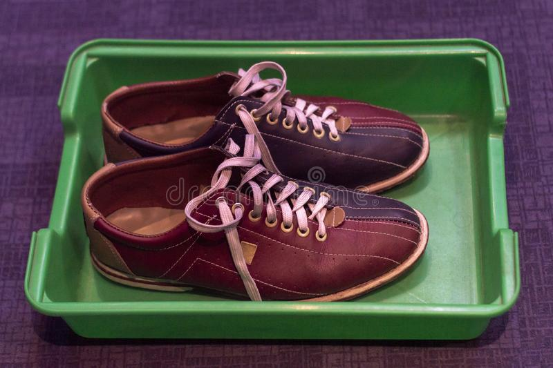 Multicolored leather shoes with laces, a pair, for playing bowling in a plastic tray royalty free stock images