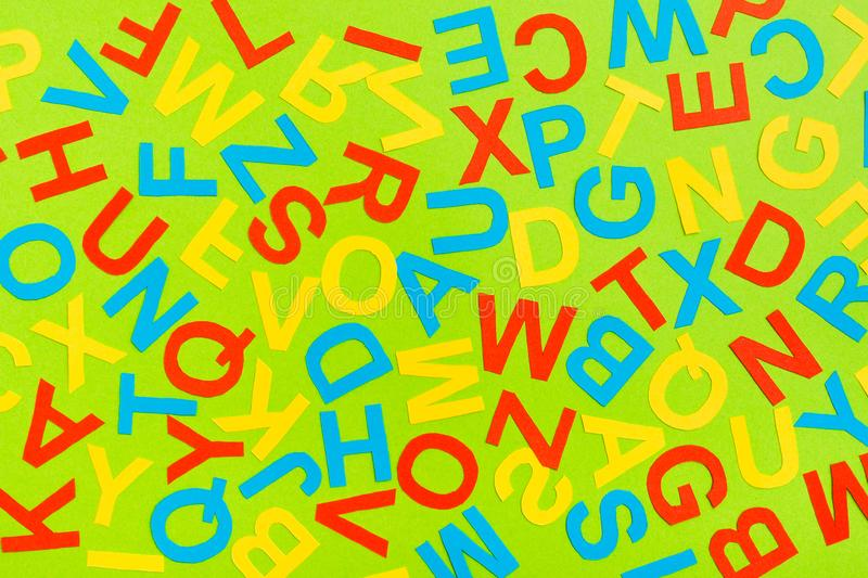 Multicolored letters of the English alphabet cut out of cardboard laid out randomly. On a green background royalty free illustration