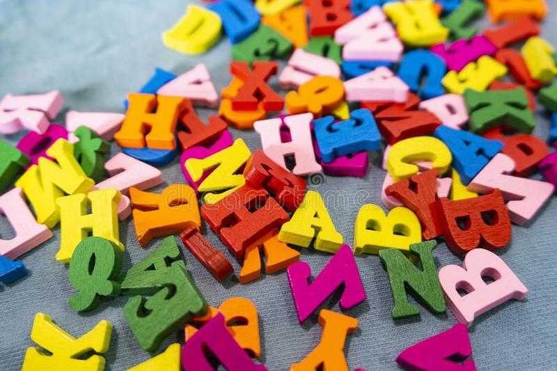 Multicolored letters of the English alphabet are scattered on the table.  stock image