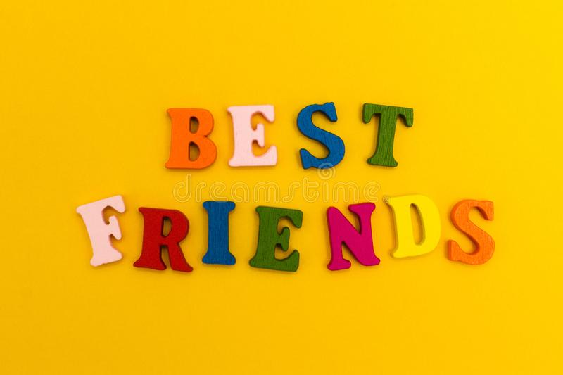 Multicolored letters on a yellow background. Best friends stock photography