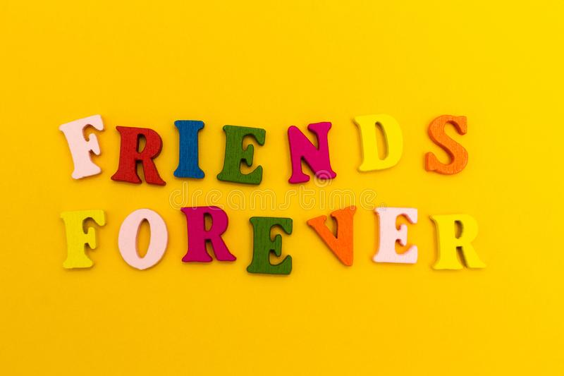 Multicolored letters on a yellow background. Friends forever.  stock photos