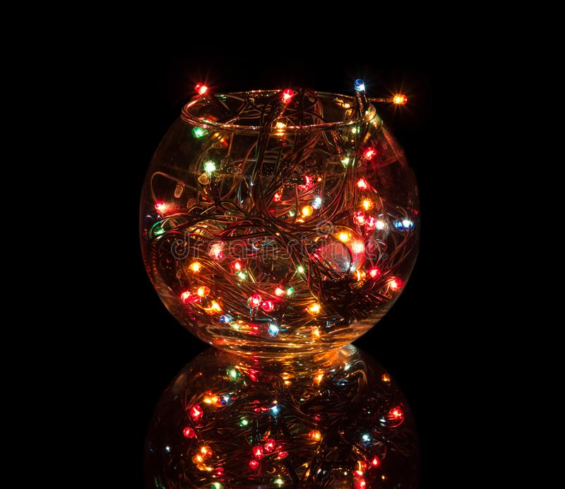 Multicolored lights of included garland glow in glass bowl isolated on black. Background stock photos