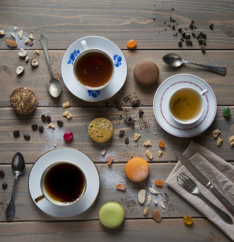 Multicolored Macarons, koppen met zwarte en groene thee en met koffie, uitstekende lepels, vork en mes op een houten lijst met va stock foto