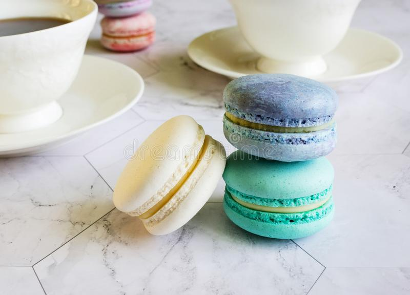 Multicolored macarons on a marble table. white cups of tea or coffee. breakfast with dessert royalty free stock images