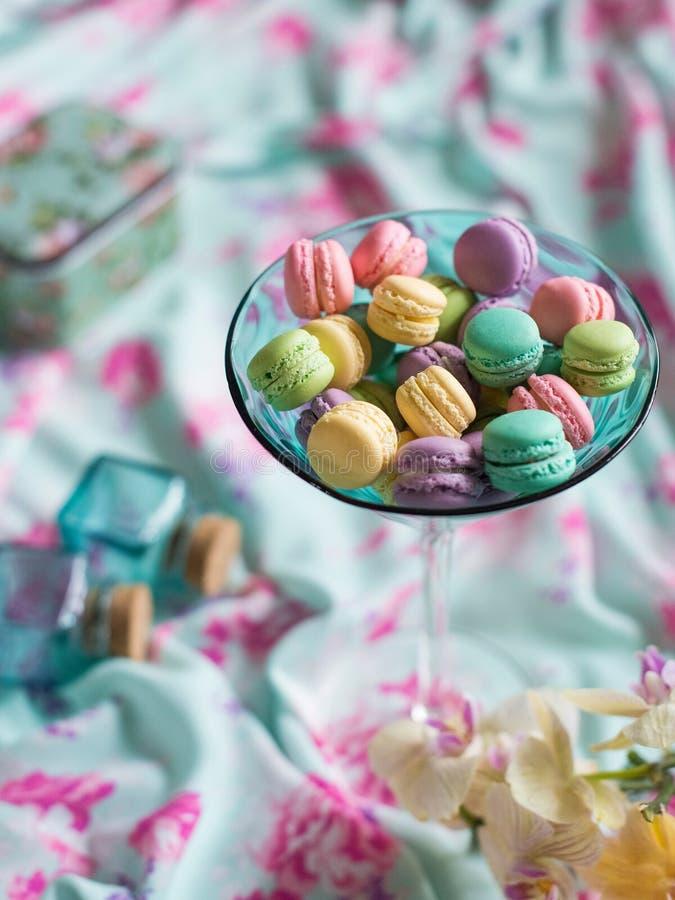 Multicolored makarons in een glas tegen een pastelkleur royalty-vrije stock foto's