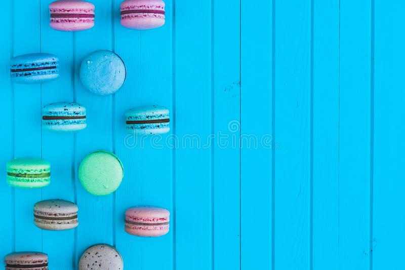 Multicolored makarons of macarons in pastelkleuren liggen in gewankelde orde op een blauwe houten achtergrond op de linkerzijde,  royalty-vrije stock fotografie
