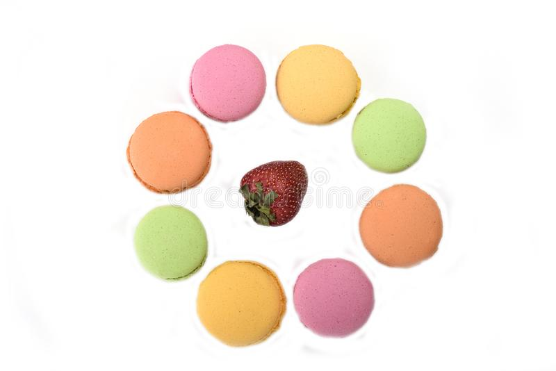 Multicolored makarons rond de aardbei stock foto's