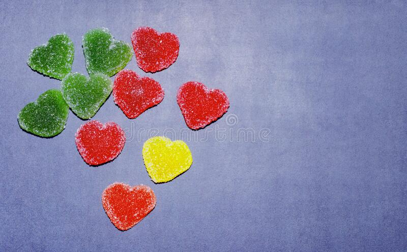 Multicolored marmalade candies in the shape of a heart on a blue chalkboard background. Marmalade in sugar, isolate. Mine Space,. Multicolored marmalade sweets royalty free stock photography