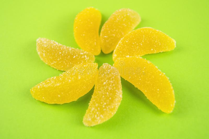 Multicolored marmalade, laid out in the form of a flower on a light green background stock images